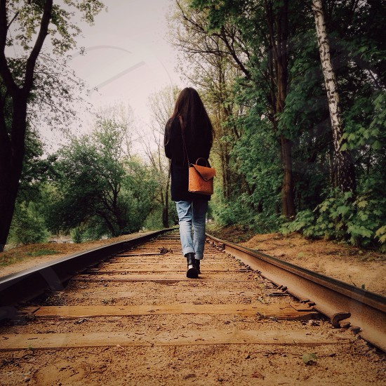 woman with brown long hair in black jacket and gray denim jeans walking in middle of rail road track during daytime photo