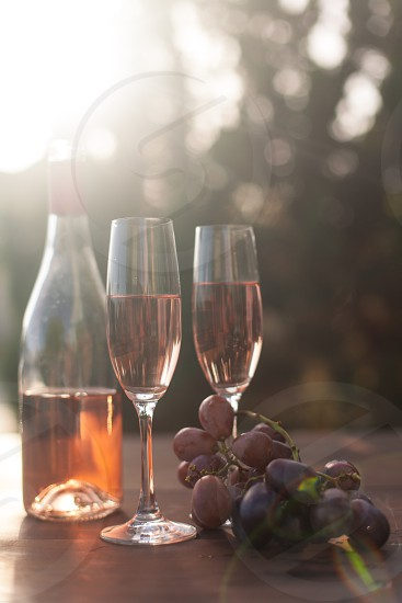 two champagne flutes with rose wine next to the bottle and purple table grapes surrounded by trees under the sun photo