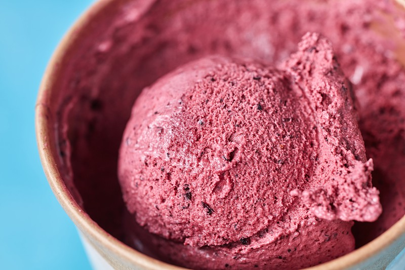 A scoop of healthy homemade berry ice cream in a paper cup on a blue background macro photo. Top view photo
