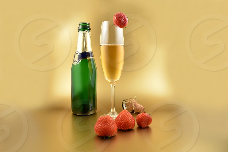Glass of champagne with strawberries. Champagne on a golden background with copy space for text. Festive golden background. Valentines Day concept photo