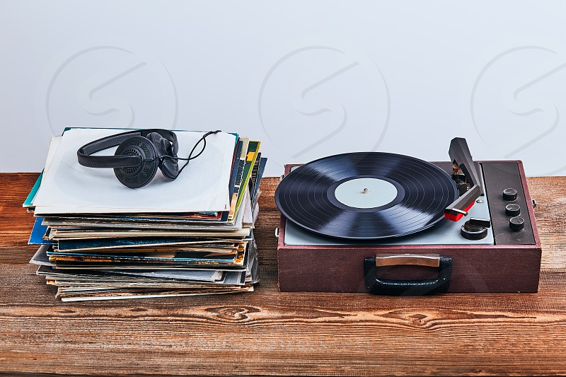 Stack of many black vinyl records turntable vinyl player and headphones put on the stack. Classic stereo set. Candid people real moments authentic situations photo