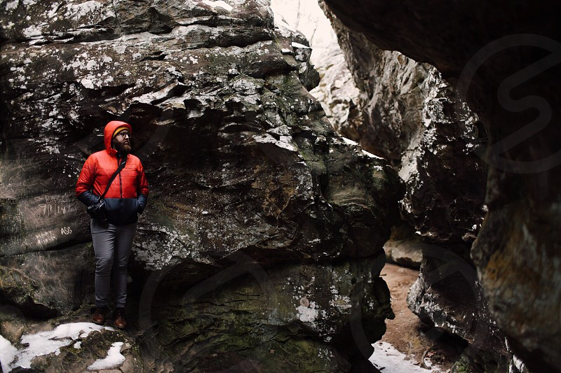 man wearing a red hooded jacket standing on a rock surrounded by rock walls photo