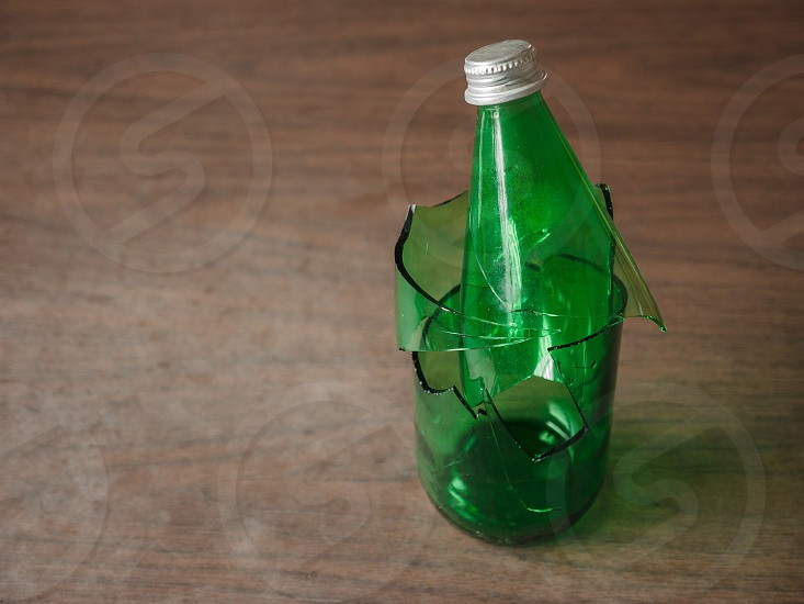 Green broken bottle on a table in the house photo