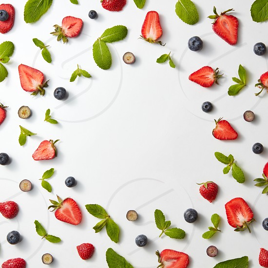 Frame of colorful composition with red ripe strawberries blueberries and green spring leaves of mint isolated on white background. Top view with copy space photo