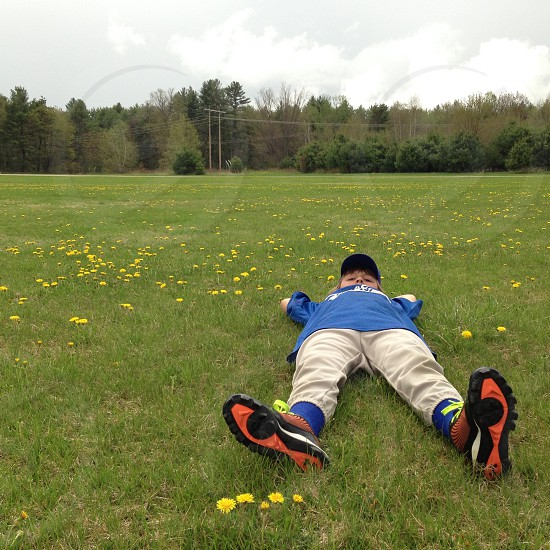 Little league layer lying in the grass photo