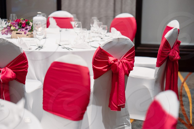 Wedding reception dinner table setup in white and red theme Spandex white cover chairs with red sash organza photo