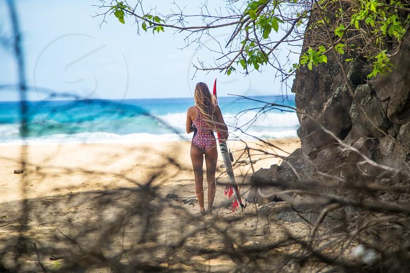Female surfer at a beach on Fernando de Noronha islands Brazil. Paradise. photo