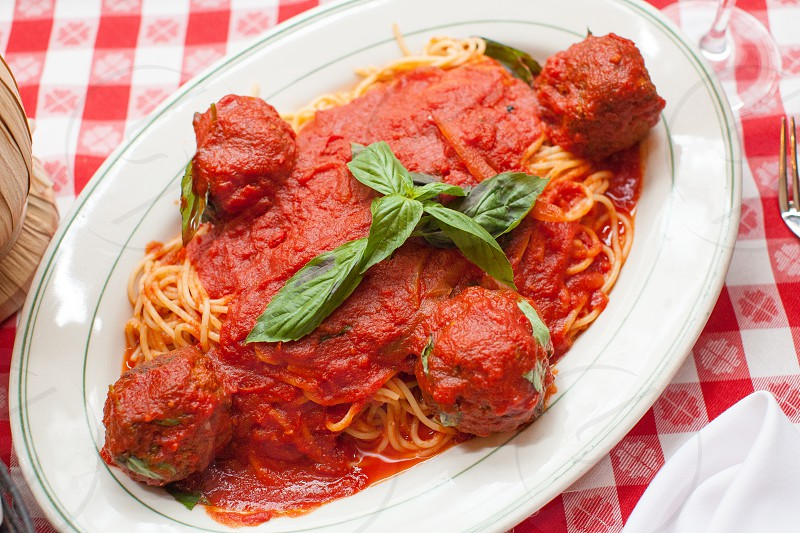 pasta with meatballs and red tomato sauce with basil leaf on top photo