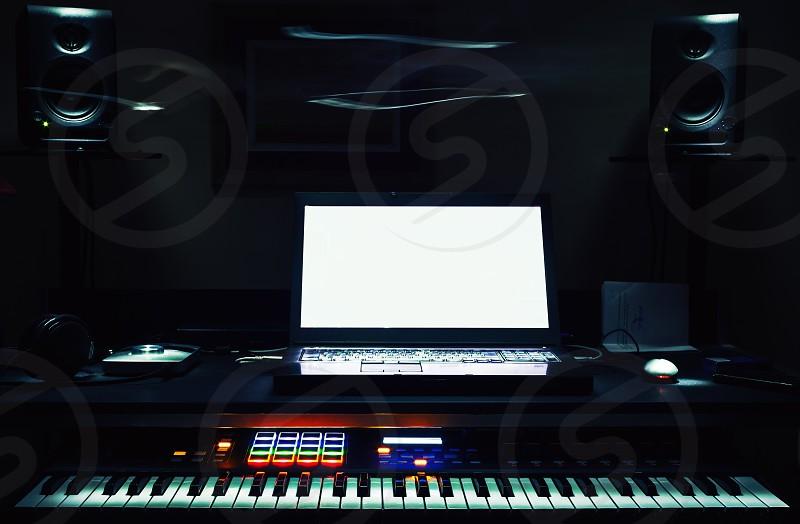 Mini home studio midi controller and laptop on table. photo