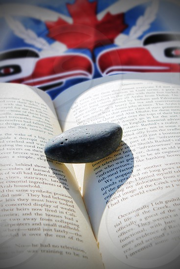 An open book with a single stone with a Native Canadian design in the background photo