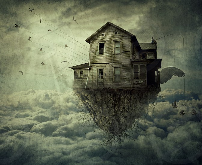Boy with a fishing rod standing on the roof of a flying house ripped from the ground and a flock of birds carrying the house over the clouds. Adventure journey and discover concept. photo