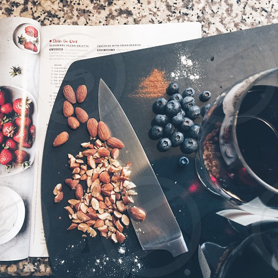 almond nuts near black berry and stainless steel kitchen knife on black cutting board photo