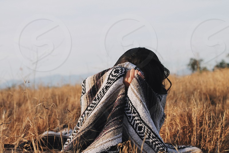 woman sitting on brown grass covering body with black grey and brown tribal cloth under grey skies photo