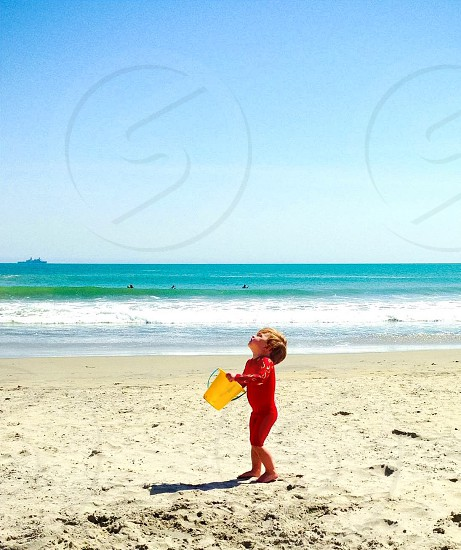 boy in red rash guard with yellow pail on the beach under blue sky photo