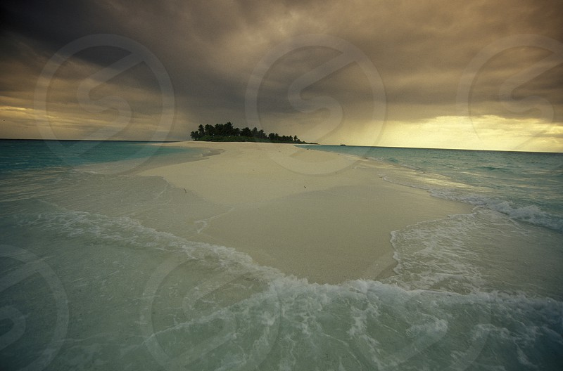 a beach with the seascape of the island and atoll of the Maldives Islands in the indian ocean. photo
