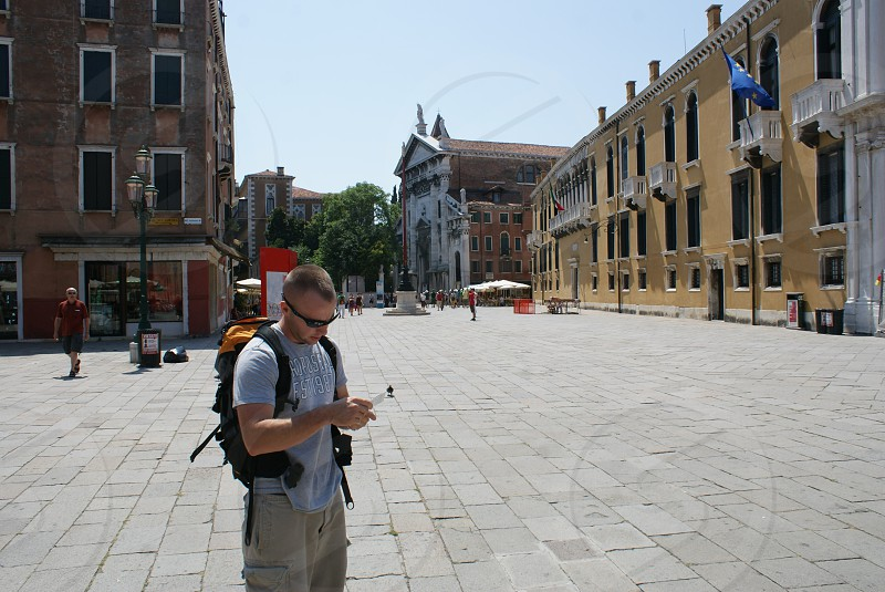 man in grey t shirt and brown shorts with black backpack standing photo