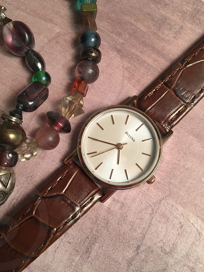 brown leather strap silver analog watch beside brown and yellow beaded bracelet on brown surface photo