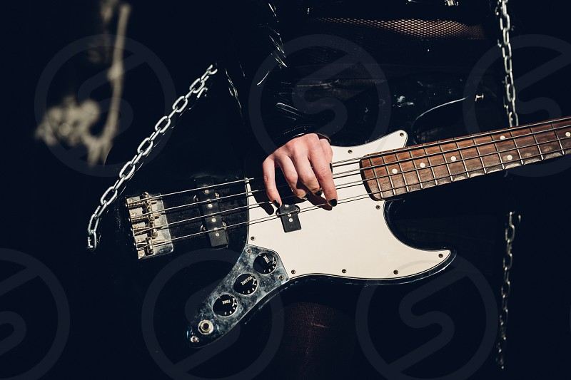 low light photography close up view of a musician holding white and black 4 string electric bass guitar photo