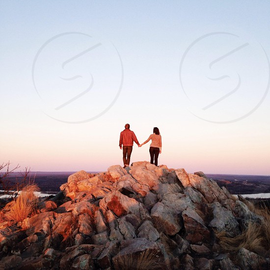 2 couple holding hands on top of rock mountain photo