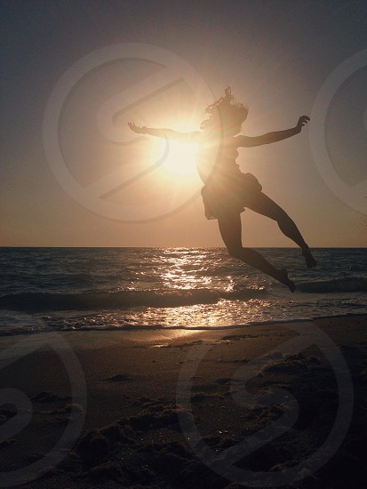 girl jumping on beach view photo