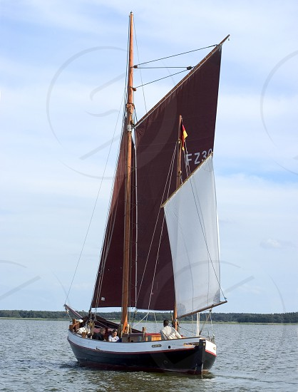 sailboat on open water maroon and white sail photo
