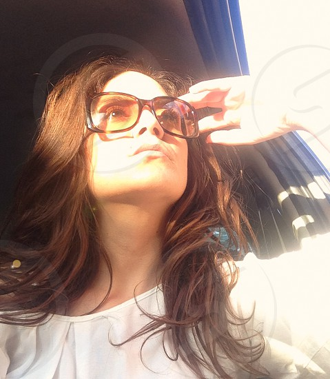Pretty woman with sunglasses in sunray photo