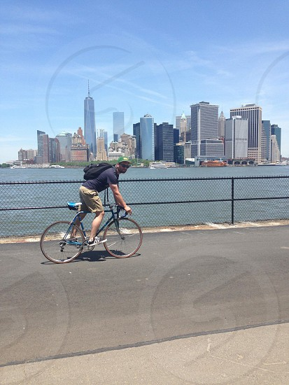 man wearing blue crew-neck t-shirt and brown shorts riding a blue city bike near chain link fence and body of water during daytime photo