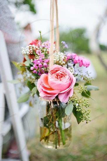 Flower arrangement in jar hanging on chair in wedding aisle  photo