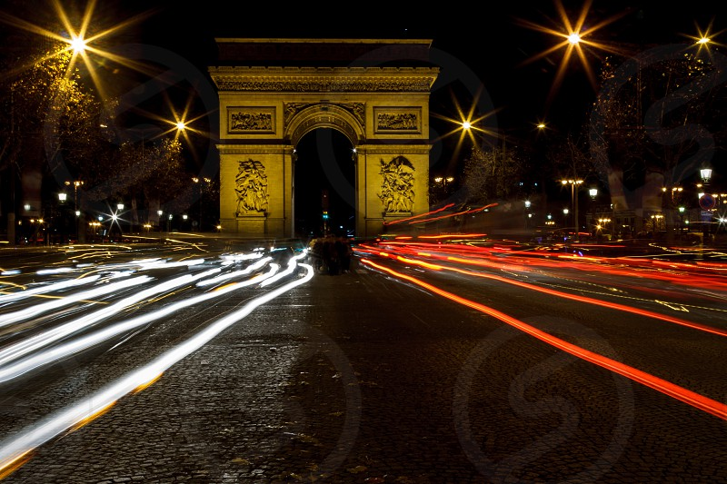 A photo taken by night in France in Paris next to the Arc de Triomphe. I was standing in the middle of the road to take and see the white and red light trails left travelling on the Champs-Elysées. photo