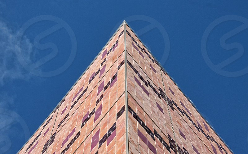 Looking up at the sharp corner of a modern brick building photo