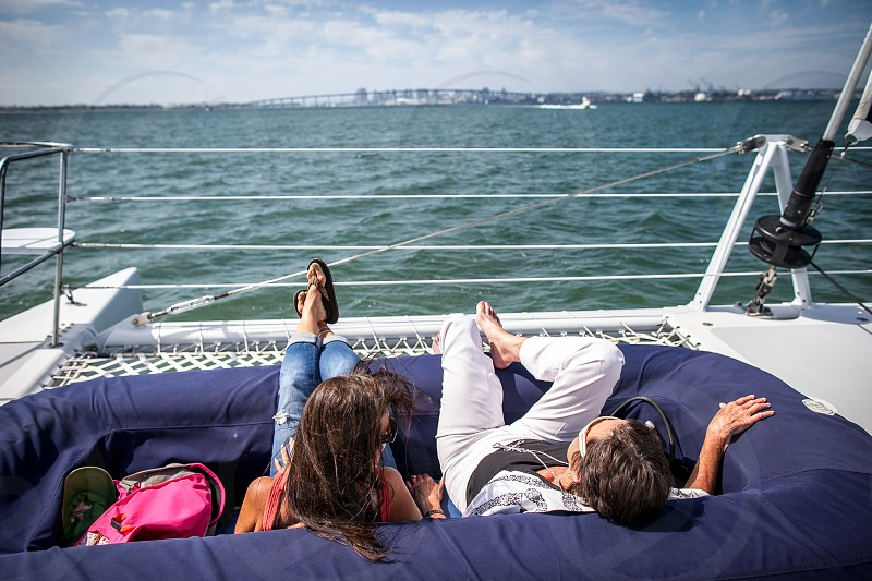 A couple relaxes on their catamaran with San Diego in the background. photo