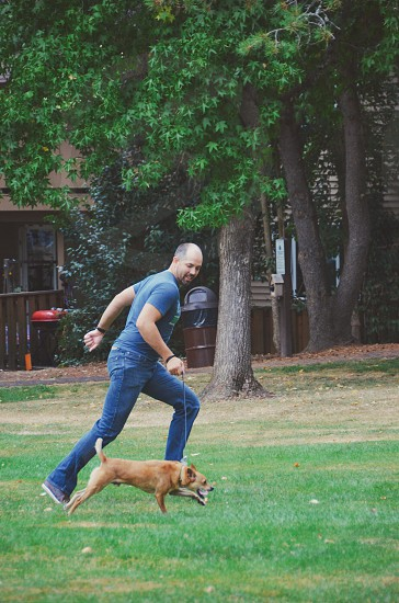 Man gentleman 30 something male running with dog in park everyday life simple life photo