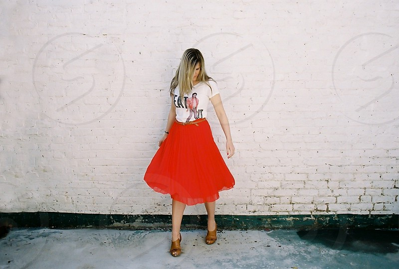 woman in white crew neck t shirt and red maxi skirt near brick wall photo