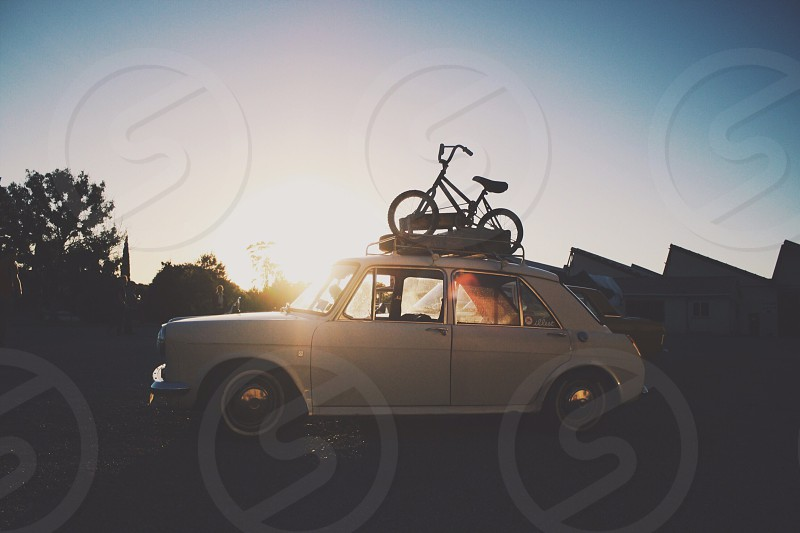 bicycle on top of white vintage car  photo