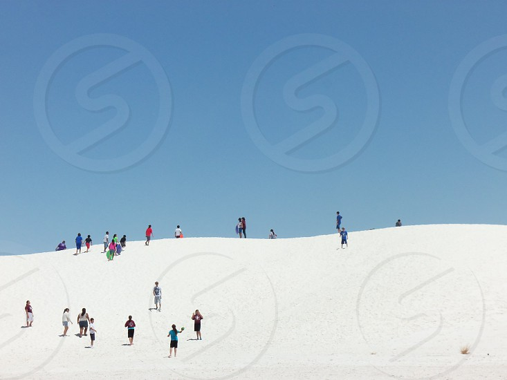 People sliding down dunes of White Sands NM photo