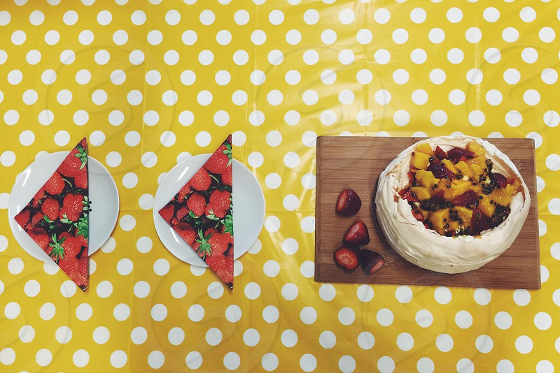 Traditional pavlova with fruit topping (mango strawberry and passionfruit) on a yellow polkadot tablecloth setting. photo