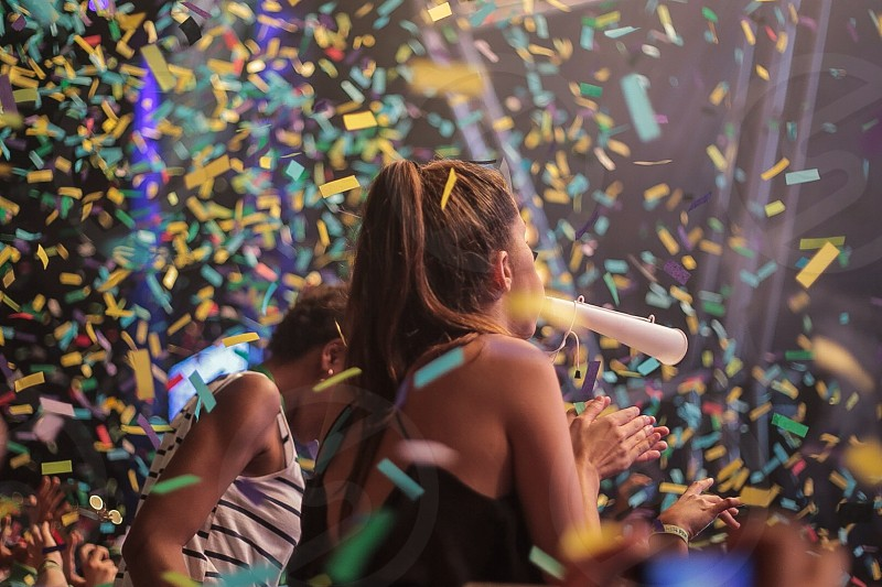 a woman wearing a black shirt standing in the middle of yellow green falling confetti photo