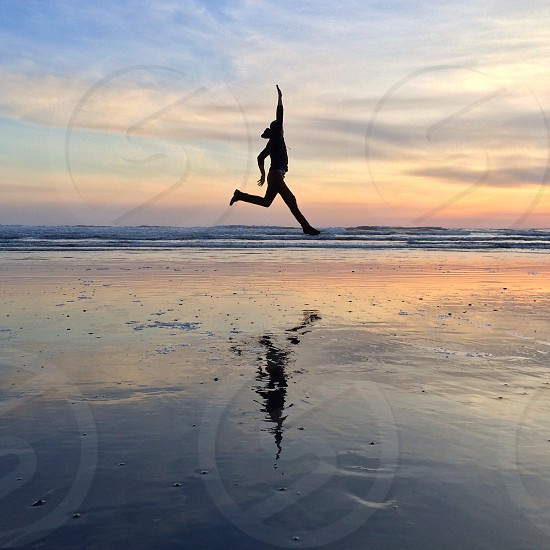 person in hoodie jumping on a brown sandy beach shore during orange sunset photo
