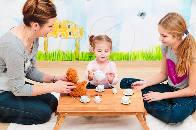 Little girl playing with her mother and elder sister at tea party using child's tea set photo