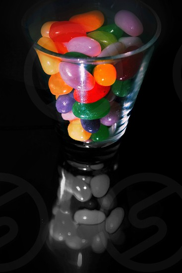 A glass full of Jellybeanscandycolorsreflections photo