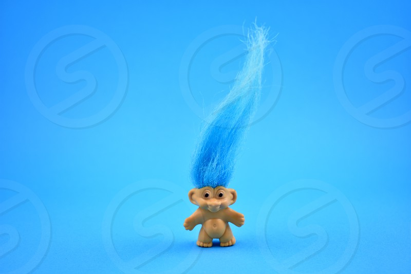 Troll figure. Elf on a blue background. Troll with blue hair. Troll toy images photo