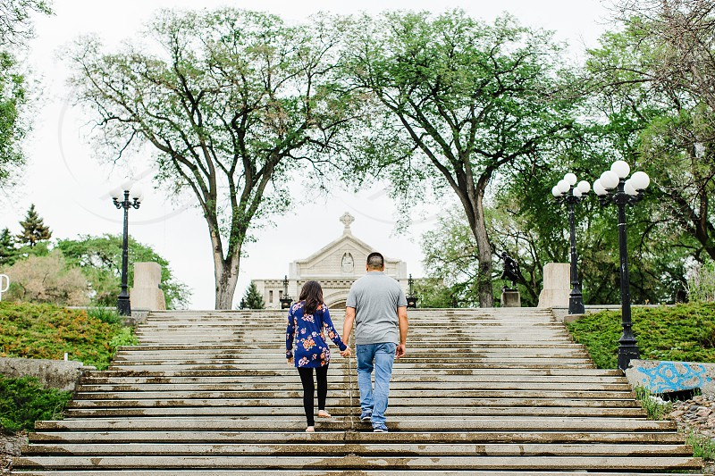 A couple hold hands and walks up stairs towards a cathedral in Winnipeg Manitoba. photo