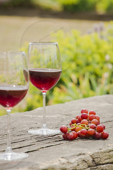 Two glasses of red wine (Rioja) next to a bunch of red grapes over a rustic wooden table. photo