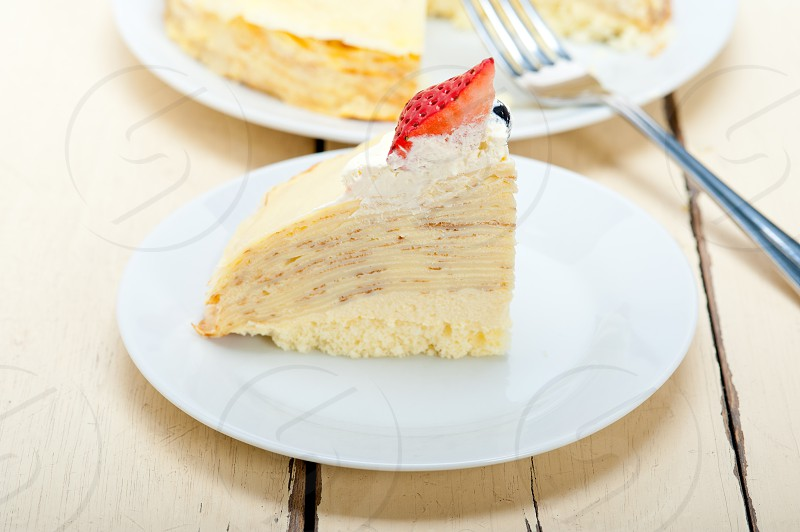 crepe pancake cake with whipped cream and strawberry on top photo