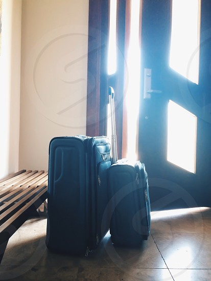 view of blue luggage bags beside wooden door photo