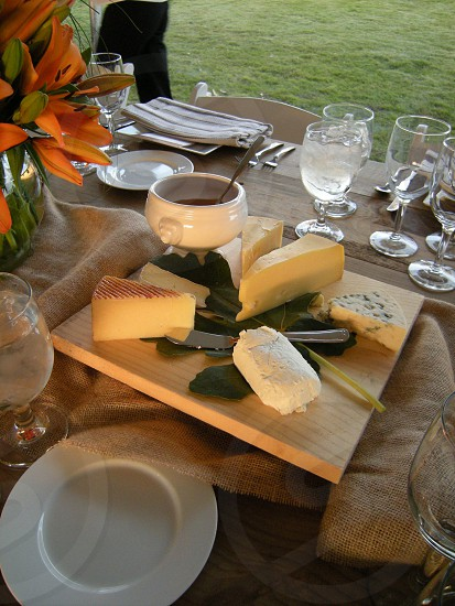 Cheese board with honey pot on wooden table with dishes and burlap photo