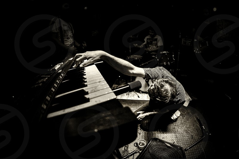 Savona Italy 23/02/2019: Black and white picture of a musician playing piano in a dramatic position during a live music event. photo