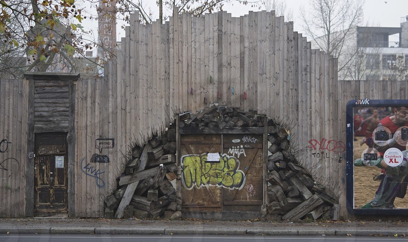 yellow grafitti on brown doors on high built wood plant wall photo