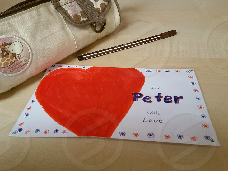 valentine's day. love. romance. girl loves boy. teenage love. message. letter. card . envelope .heart. red. painted. schoolgirl. pencil bag. wooden table photo