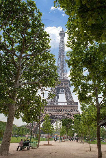 Bottom up view of Eiffel tower dream with clouds and a beautiful green park against the blue sky Paris France photo